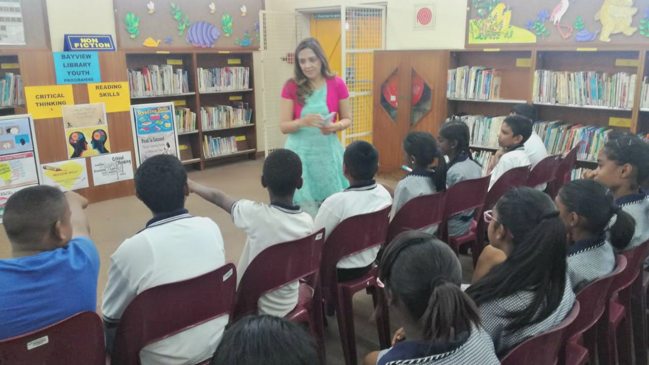Dr Mariam Seedat-Khan with Grade 7 learners at Bayview Library.